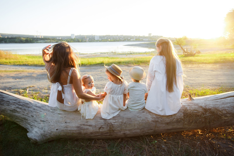 A large lesbian family with children. The family sits with their backs to the camera on a fallen log against the backdrop of the lake.