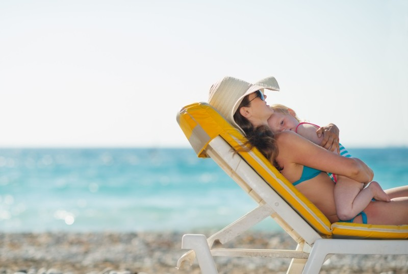 14246341 - mother with baby laying on sunbed on beach