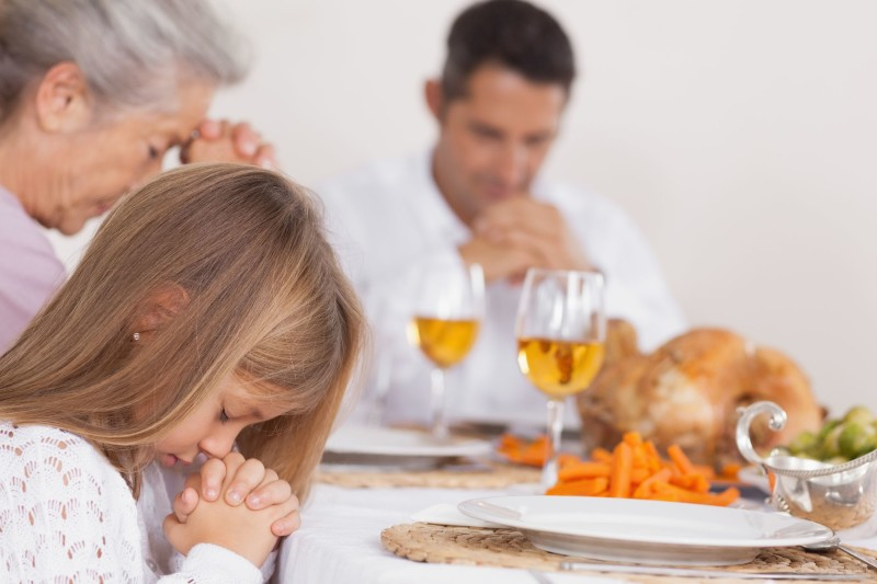 18121559 - little girl saying grace with family before thanksgiving dinner