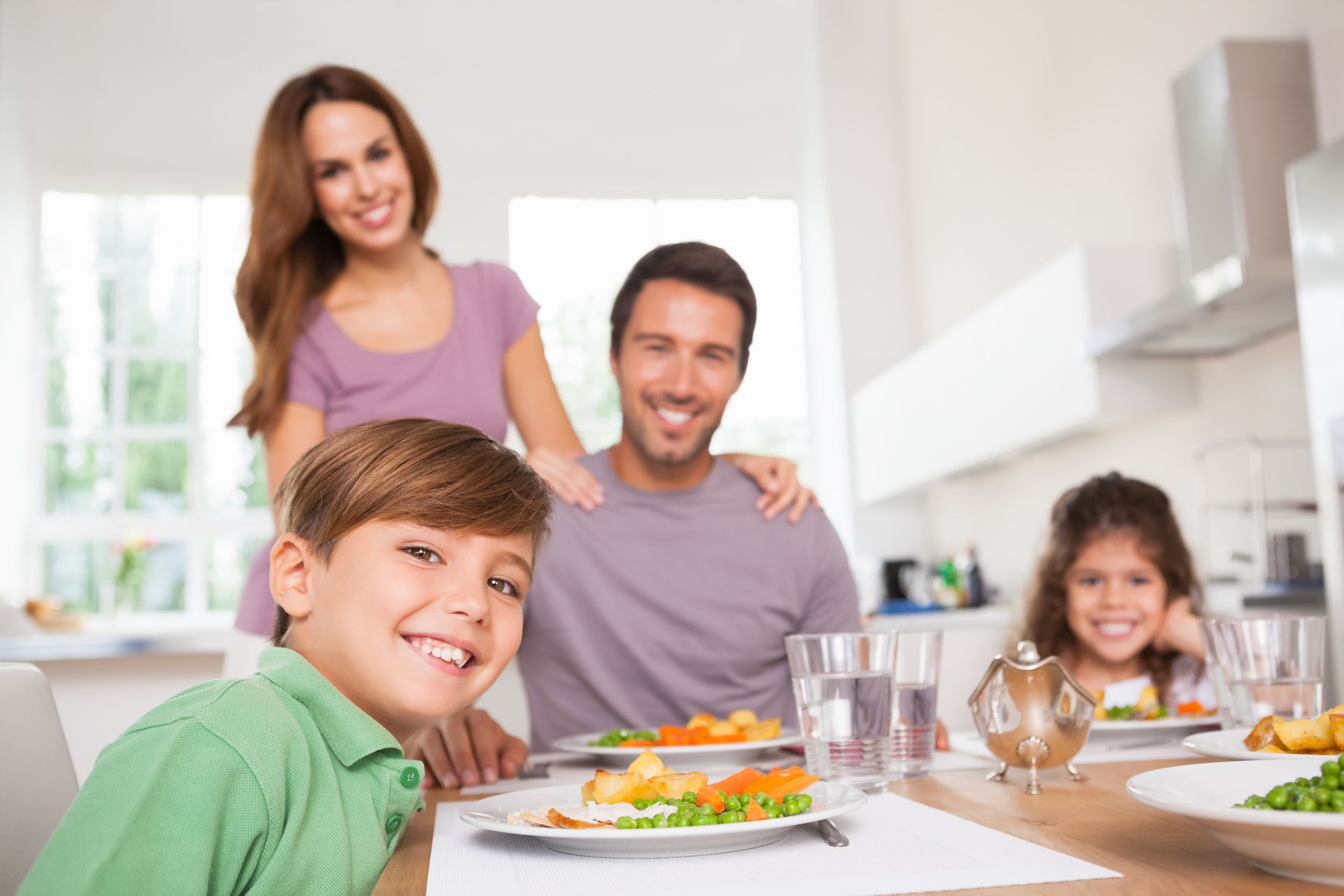 18122452 - family looking at the camera at dinner time in kitchen