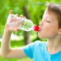 20451288 - boy drinks water from a bottle outdoors