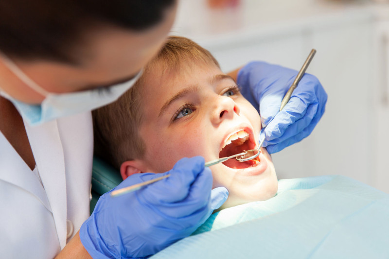 41935886 - dentist examining boys teeth close up