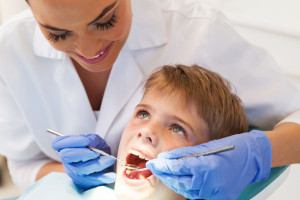 41935896 - professional female dentist examining little patient