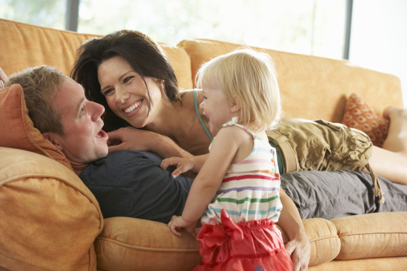 42255641 - family lying on sofa at home
