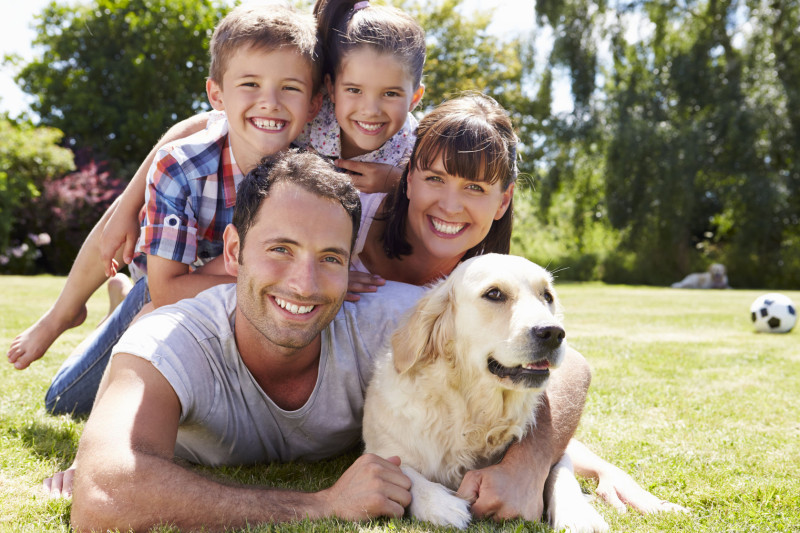 42309403 - family relaxing in garden with pet dog