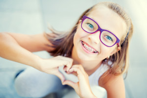 Smiling little girl in with braces and glasses showing heart with hands.