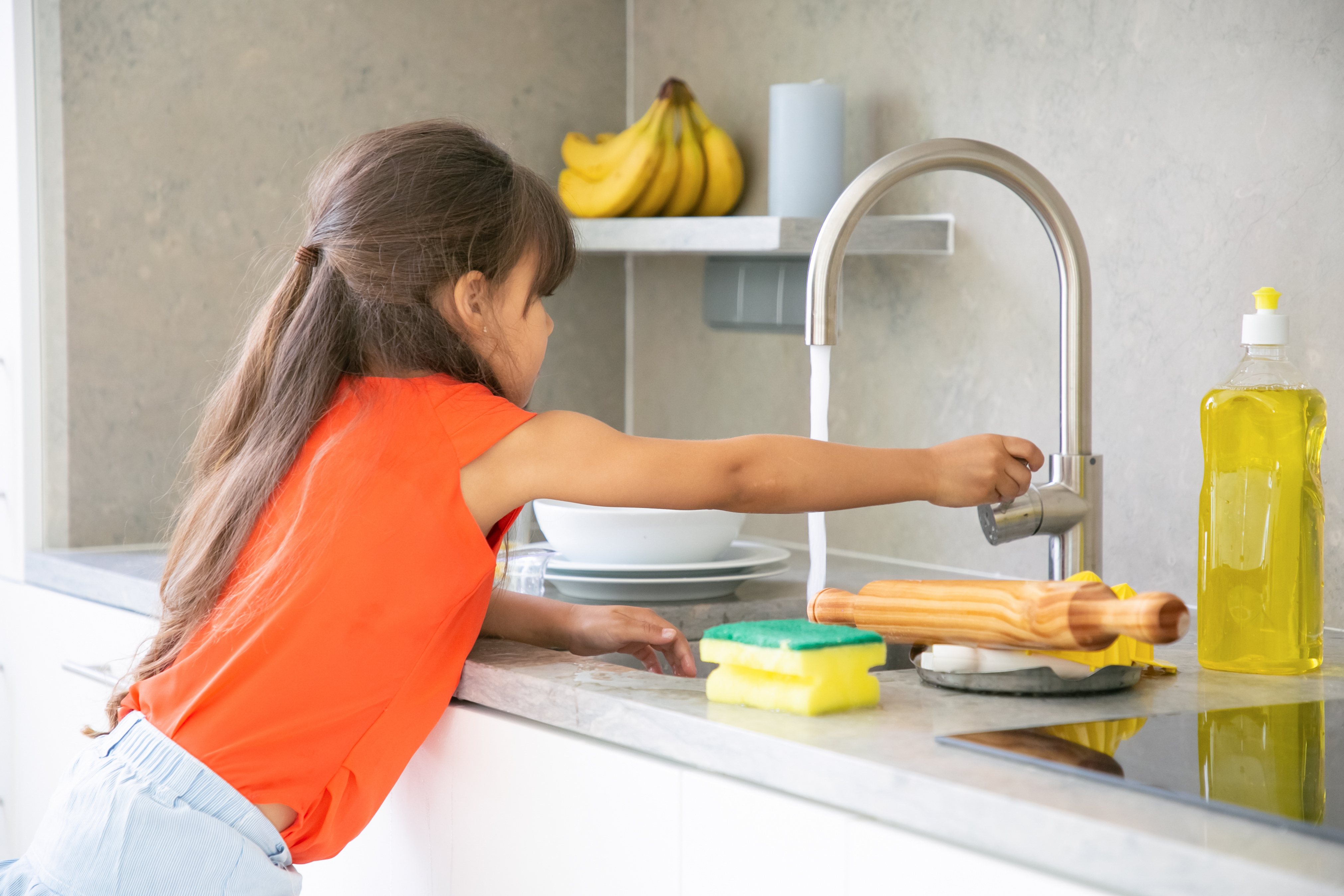 Cute little girl washing dish in kitchen by herself