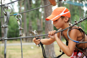 Young boy engaged climbing at the rope course.